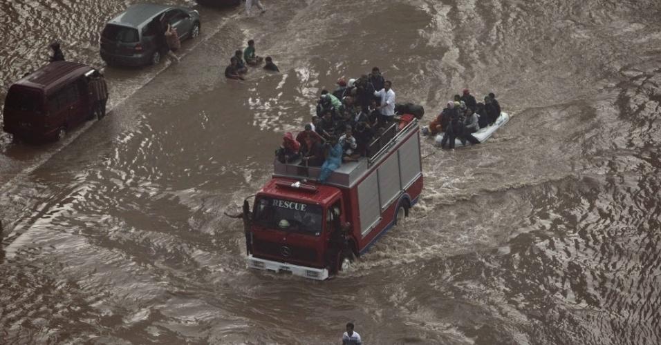 17.jan.2013 - Grupo  enfrenta via completamente alagada  em Jacarta, Indonésia.  Por causa das fortes chuvas, milhares de pessoas tiveram de deixar suas casas