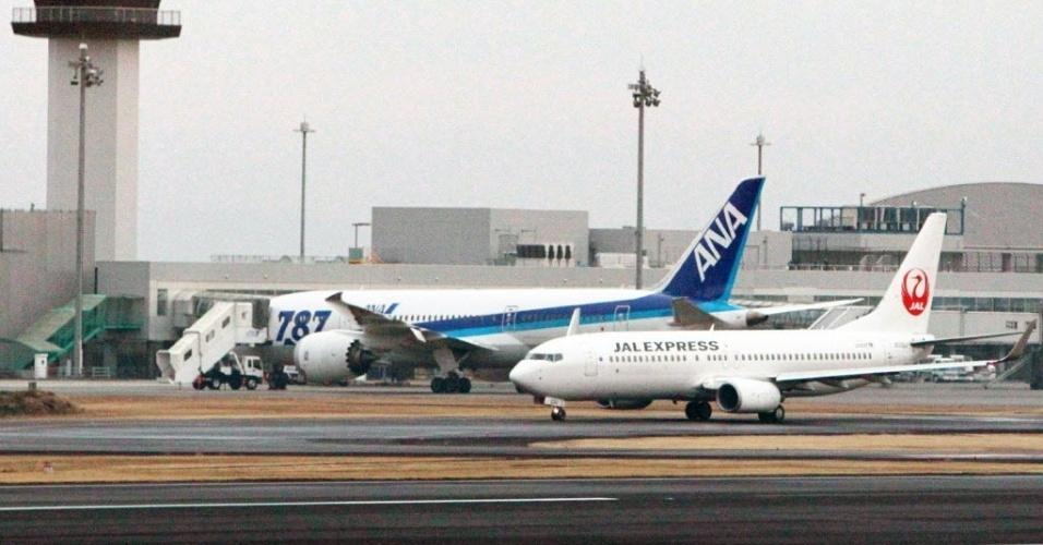 17.jan.2013 - Um avião Boeing 787 Dreamlier (à esquerda) permanecia estacionado nesta quinta-feira (17) no aeroporto de Takamatsu, na ilha japonesa de Shikoku, depois de ter feito pouso de emergência no dia anterior. Após seis incidentes parecidos em dez dias, a Agência Federal de Aviação dos Estados Unidos e o ministério japonês dos Transportes determinaram a suspensão de todas as operações com a aeronave até a conclusão de uma investigação de segurança