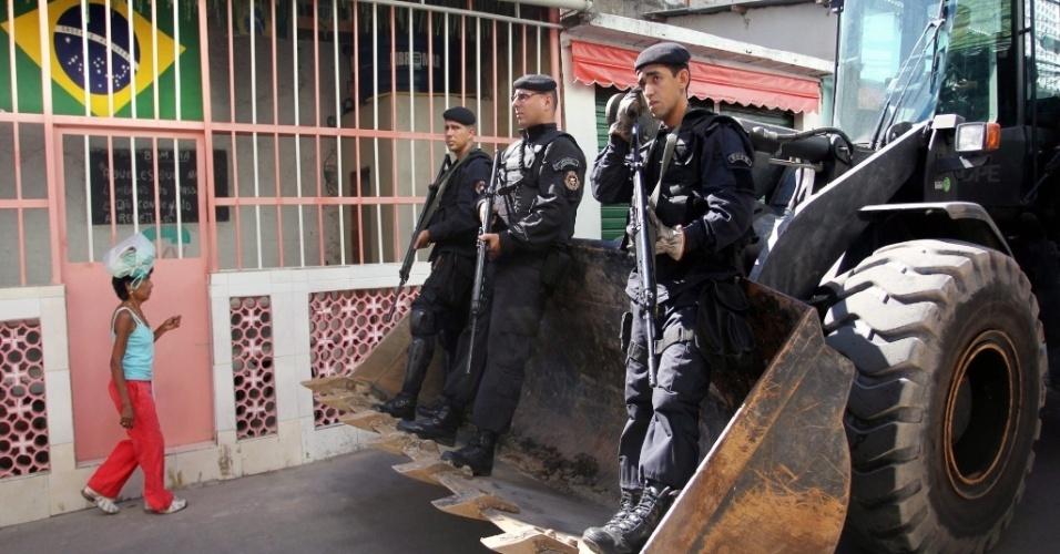 Policiais do Bope (Batalhão de Operações Especiais) pegam carona em retroescavadeira durante patrulhamento em favela do Rio de Janeiro