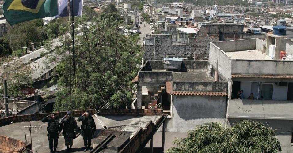 Policiais do Bope batem continência diante das bandeiras do Brasil e do Estado do Rio de Janeiro, no alto da favela do Jacarezinho, no Rio