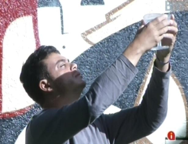 18.jan.2013 - Dhomini faz uma oferenda com o copo d'água. Entenda a religião que ele segue