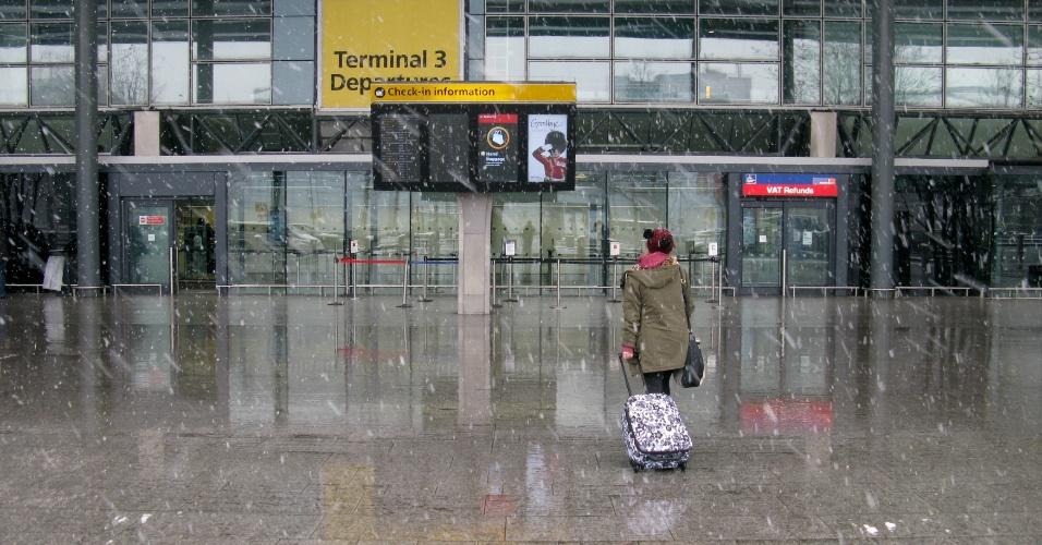 18.jan.2013 - Passageira chega ao aeroporto de Heathrow, em meio a nevasca que atinge Londres, Inglaterra, nesta sexta-feira (18). O aeroporto londrino, o de maior tráfego da Europa, cancelou 179 voos por causa das intensas nevascas, enquanto o mau tempo também afetou os serviços de trens e ônibus em todo o país