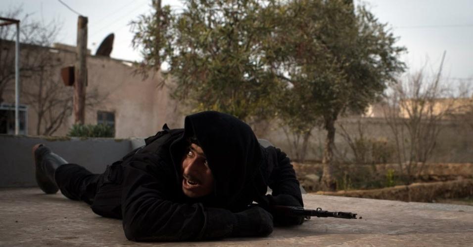 18.jan.2013 - Rebelde sírio tentam se proteger dos ataques das tropas leiais a Bashar Assad, em Aleppo, Síria