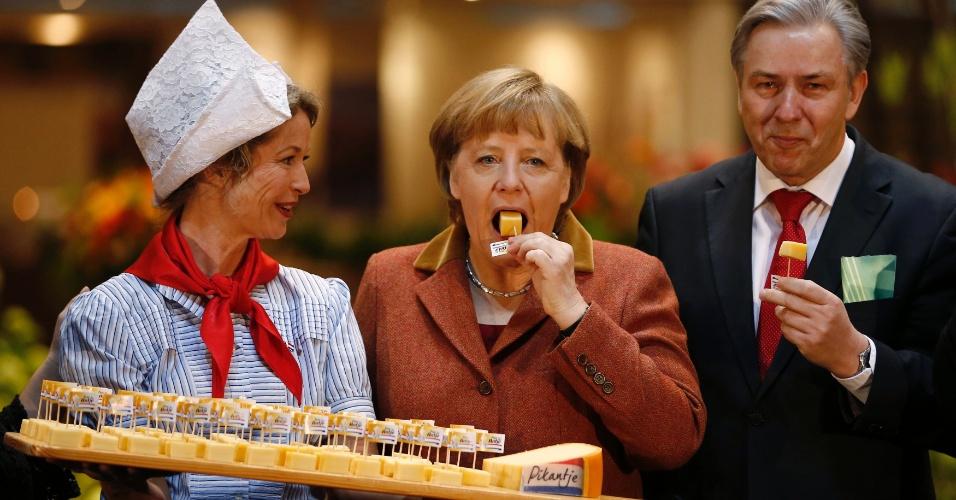 18.jan.2013-  A chanceler alemã Angela Merkel (centro) degusta um queijo durante visita a uma feira gastronômica e agrícola em Berlim, na Alemanha