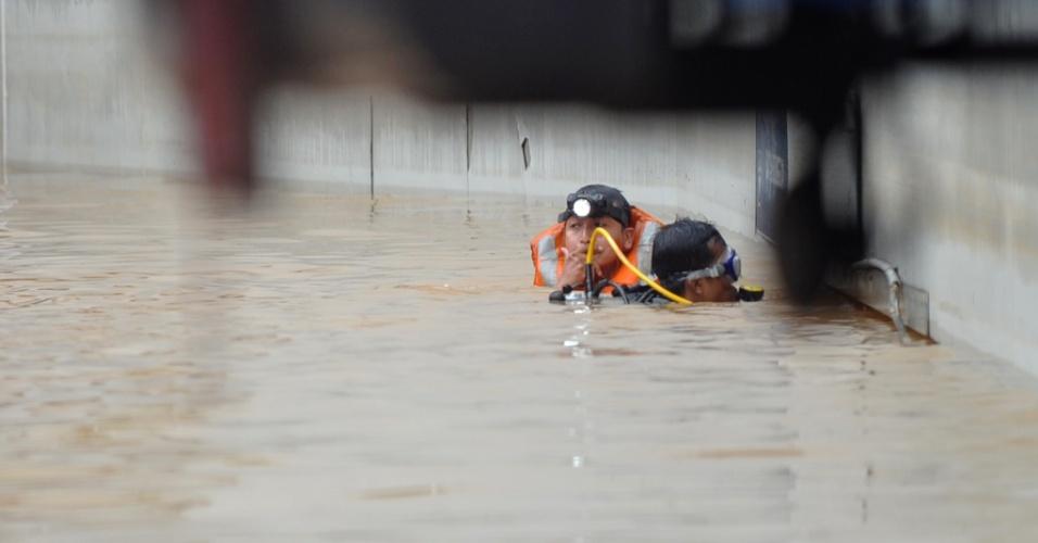 18.jan.2013- Homens da equipe de resgate buscam pessoas que ficaram presas em um túnel, em Jacarta, na Indonésia. A capital enfrenta as piores enchentes dos últimos cinco anos, que já deixaram pelo menos 18 mil desabrigados e mais de dez mortos