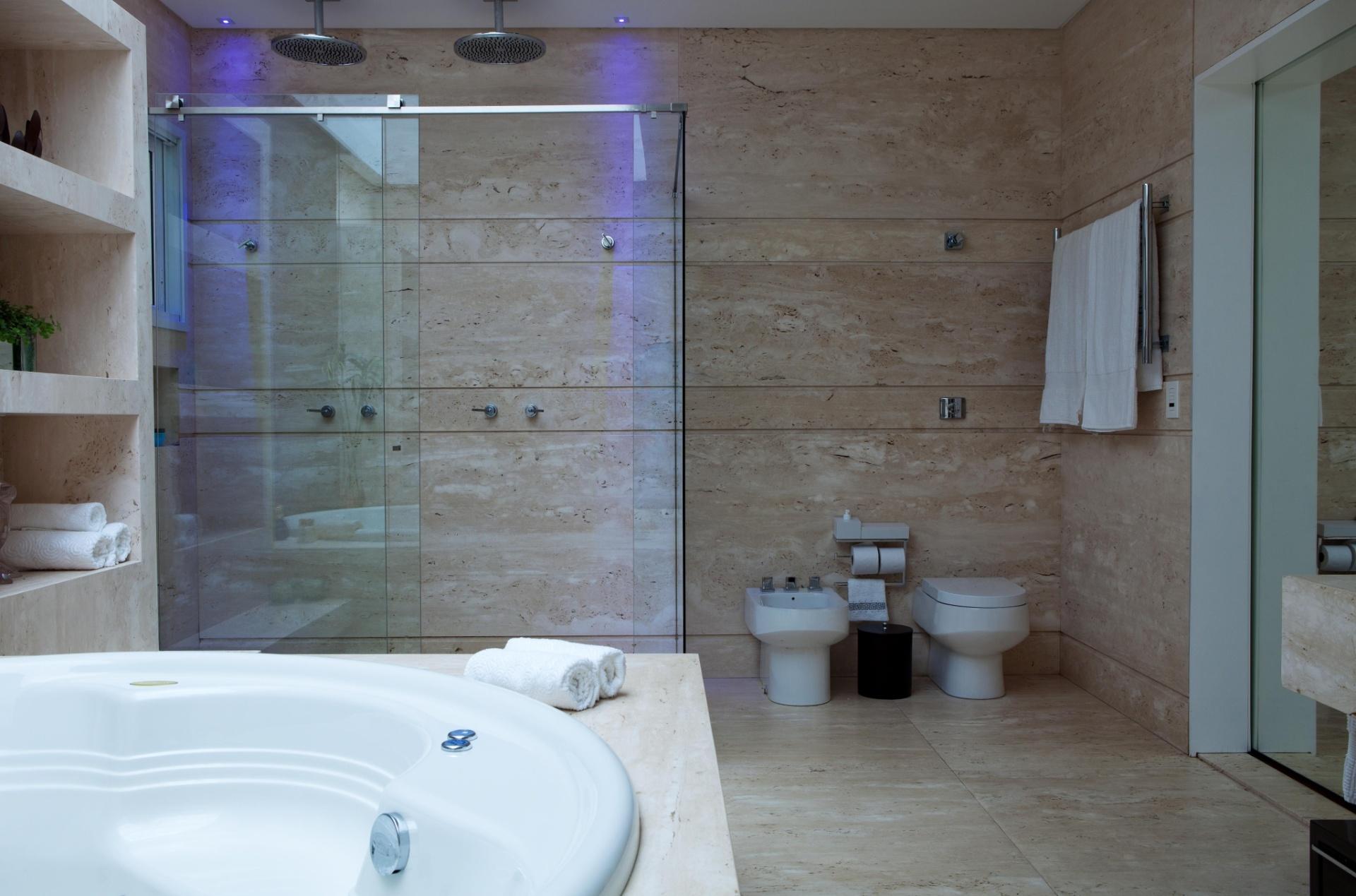 O revestimento em Limestone, que cria nichos e recobre o espaço do chão ao teto dá leveza ao banheiro da suíte máster da casa em Barueri (SP), decorada por Giseli Koraicho