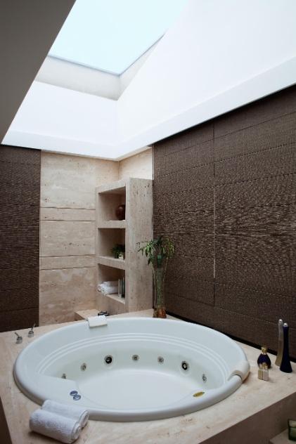 O revestimento em Limestone, que cria nichos e recobre o espaço do chão ao teto dá leveza ao banheiro da suíte máster da casa em Barueri (SP), decorada por Giseli Koraicho. Destaque para a generosa banheira com hidromassagem