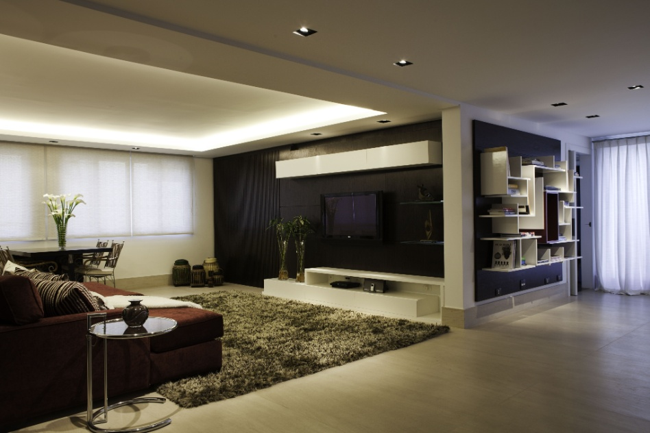 Uma sala íntima faz parte da área que abriga as suítes da casa em Barueri (SP), decorada por Giseli Koraicho. O espaço tem painéis escuros ao fundo da estante e como apoio da TV e se baseia em tons neutros. Ao contrário dos quartos, o ambiente não conta com cortinas pesadas e amplas