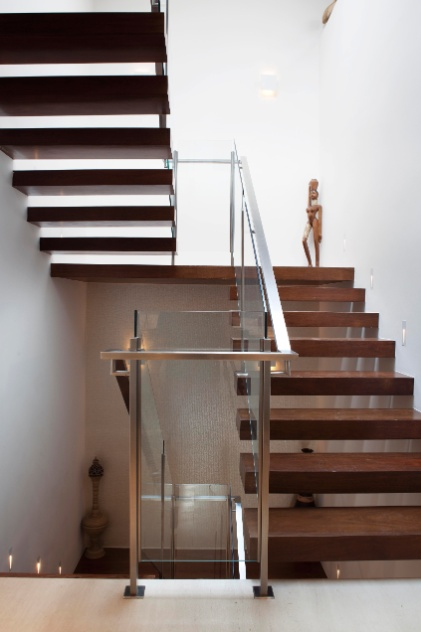 O guarda-corpo de vidro e metal dá amparo aos degraus de madeira da escada que leva ao piso superior da casa em Barueri (SP), decorada por Giseli Koraicho. Atente para as luzes direcionais à altura do passo que iluminam o caminho dos usuários