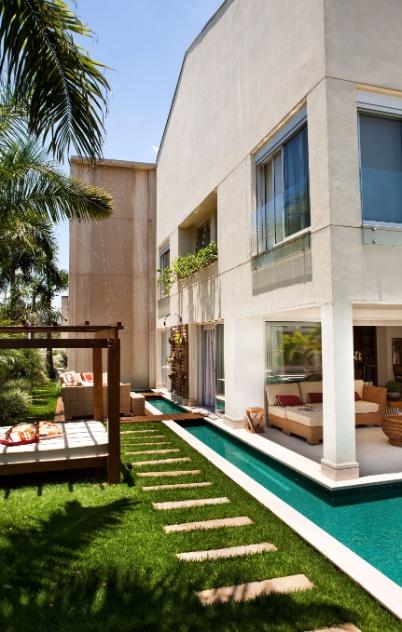 O paisagismo da casa em Barueri (SP) é assinado pela designer de interiores Giseli Koraicho e se baseia em exemplares tropicais como palmeiras, orquídeas e árvores frutíferas. Ao lado da construção, um espelho d'água dá leveza ao volume construído
