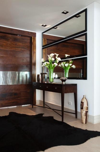 No hall de entrada da casa em Barueri (SP), decorada pela designer de interiores Giseli Koraicho, há uma maciça presença de madeira na ampla porta pivotante, bem como nos móveis e objetos