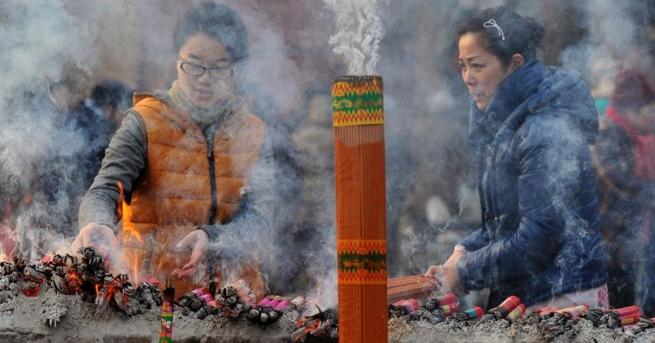19.jan.2013 - Chinesas acendem incenso em templo em Nanjing, na província de Jiangsu, durante o festival Laba