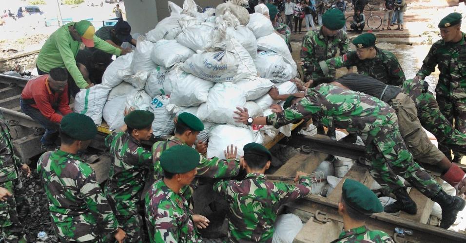 19.jan.2013 - Militares indonésios empurram pilhas de sacos de areia para serem usados como barreiras contra rio que transbordou em Jacarta após fortes chuvas na região