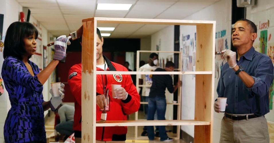 """19.jan.2013 - O presidente americano, Barack Obama, pinta estante ao lado da mulher, Michelle, em uma escola primária de Washington. A atividade faz parte do """"Dia de Serviço"""", marcado por ações voluntárias em todo o país"""