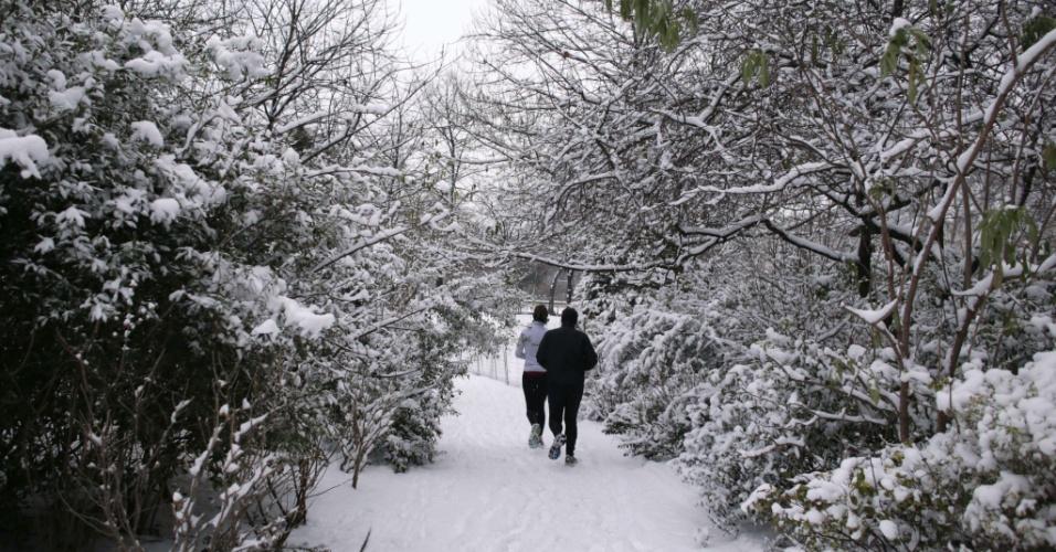 Pessoas correm em parque coberto de neve próximo à torre Eiffel, em Paris