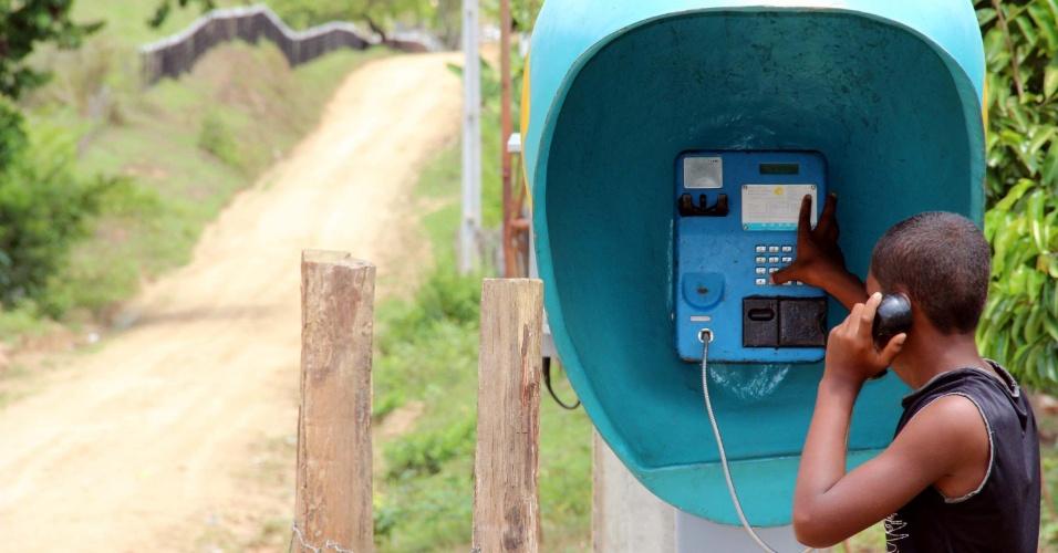22.jan.2013 -  Garoto usa o único telefone público do assentamento Flor da Terra, zona rural de Jequié (BA). O aparelho só serve para chamadas de emergência. Não faz, nem recebe ligações para celular.  No local moram 35 famílias que dependem do aparelho para se comunicar
