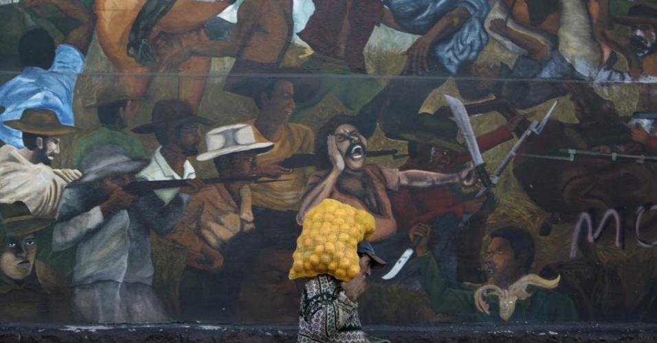 22.jan.2013 - Homem com saco de laranja nas costas passa em frente a mural em prédio de estação de rádio em Tegucigalpa (Honduras) que retrata luta entre agricultores e proprietários de terras
