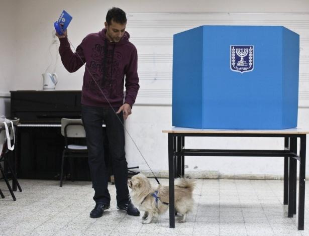22.jan.2013 - Homem leva cachorro para cabine de votação em um colégio eleitoral de Tel Aviv, em Israel, nesta terça-feira (22) January 22, 2013. Mais de 5,5 milhões de israelenses devem ir às urnas. Pesquisas recentes apontaram o primeiro-ministro, Benjamin Netanyahu, como favorito