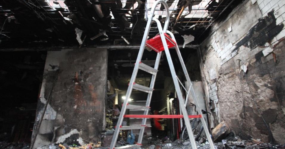 22.jan.2013 - Moradores arrombam portas para saquear o supermercado Bonsucesso, no bairro Vila São José, em Cubatão (SP. Parte do estabelecimento já havia sido destruído por incêndio na madrugada)