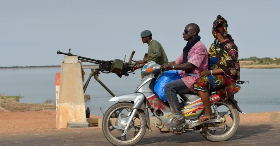 22.jan.2013 - Na garupa de uma moto, mulher obseva soldado do Exército de Mali controlando ponto estratégico em ponte, em Markala (270 km de Bamaco), Mali