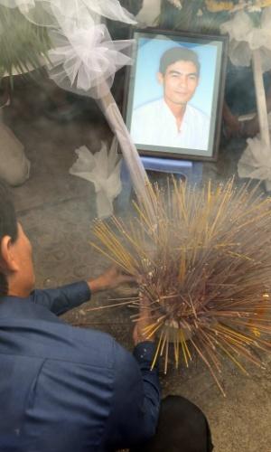 22.jan.2013 - Presidente do Sindicato do Comércio Livre do Camboja, Chea Mony (à esquerda), reza em frente a foto de seu irmão que morreu no local há nove anos, em Phnom Penh. Cerca de cem trabalhadores e sindicalistas colocaram flores e incensos no local onde o crítico do governo foi assassinado como forma de apelo pela libertação de dois homens - visto por grupos de direitos humanos como bodes expiatórios - condenados a 20 anos de prisão pelo assassinato