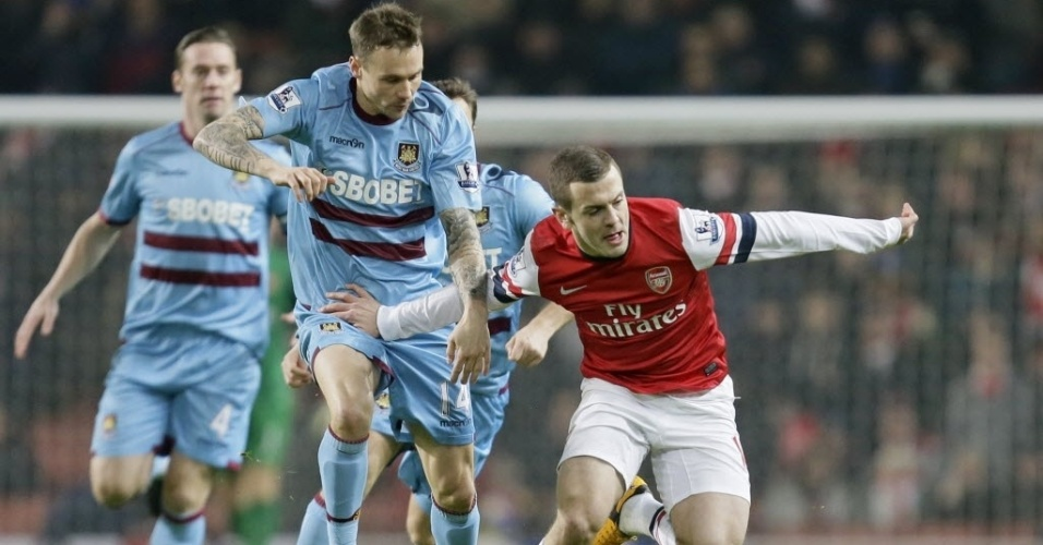 20.jan.2013 - Jack Wilshere, do Arsenal, (dir.) disputa a bola com Matthew Taylor, do West Ham, em partida do Campeonato Inglês