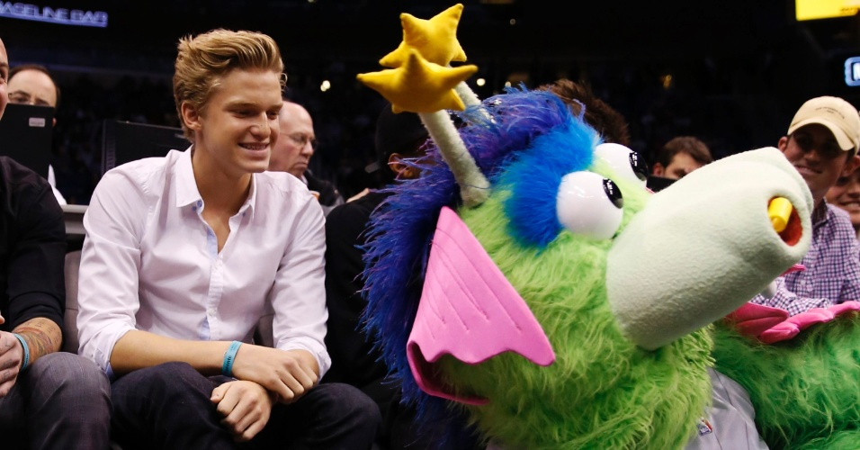24.jan.2013 - Cantor Cody Simpson posa ao lado do mascote do Orlando Magic durante jogo do time da Flórida contra o Toronto Raptors