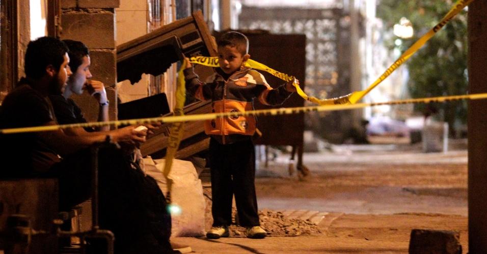 24.jan.2013 - Criança brinca com fita amarela da polícia demarcando cena de crime em Monterrey, no norte do México. Um homem e uma mulher foram assassinados em frente de casa por atiradores em um veículo. Um outro homem ficou ferido, de acordo com a imprensa local