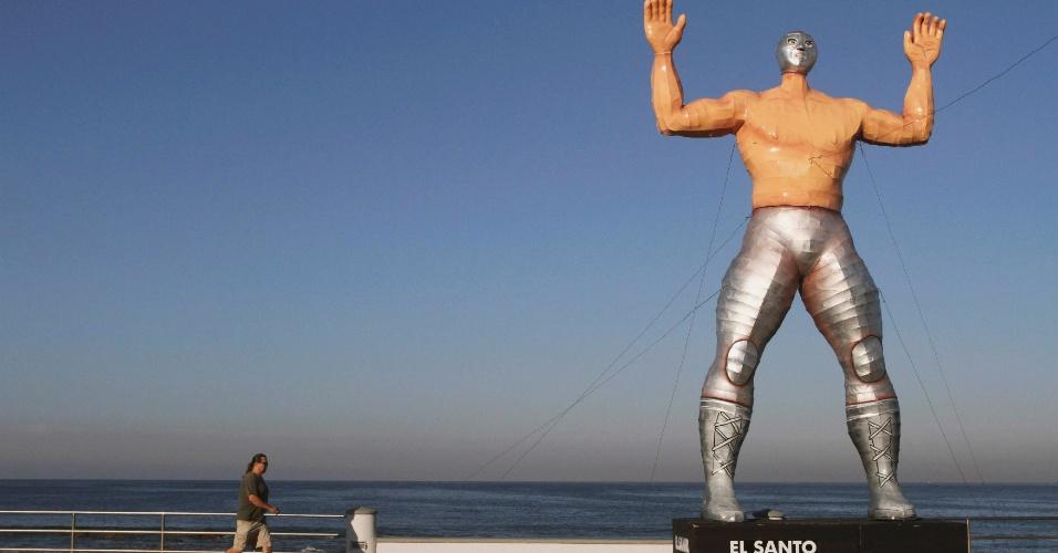24.jan.2013 - Pedestre passa por estátua gigante do lutador de 'lucha libre' El Santo na cidade de Mazatlan, na costa oeste do México. Outras sete estátuas semelhantes, de outros lutadores, foram espalhadas pela cidade para a comemoração ao carnaval