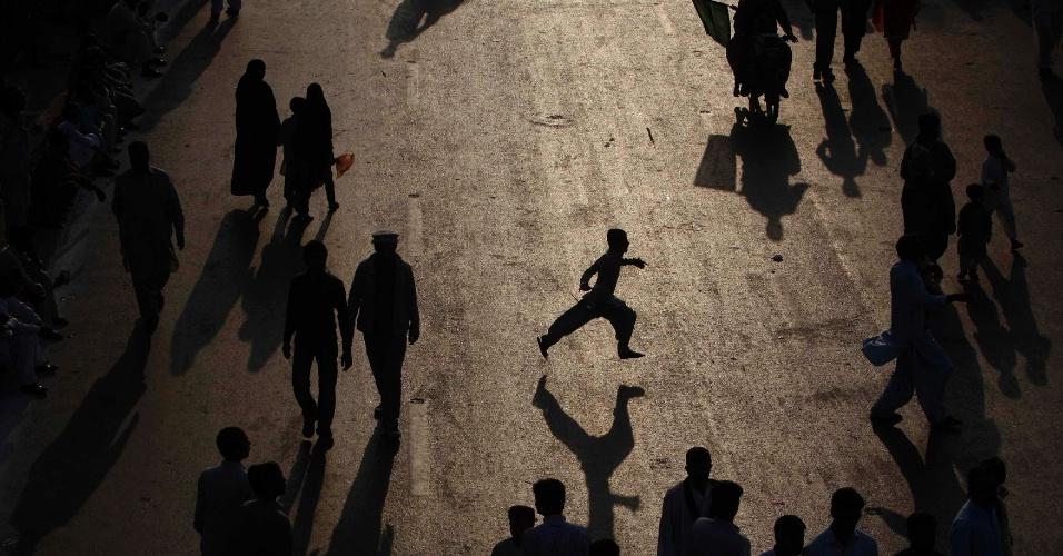 25.jan.2012- Silhueta de um garoto correndo entre os participantes da procissão pelo aniversário do profeta Maomé, para arrecadar dinheiro, em Karachi, na Índia