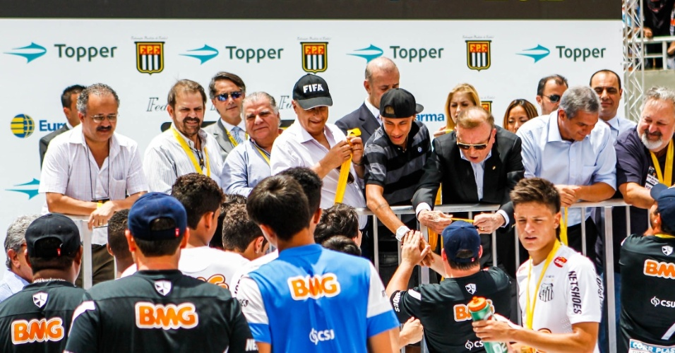 25.jan.2013 - Cercado por Marco Polo Del Nero e José Maria Marín, Neymar entrega medalhas para os jogadores do Santos campeões da Copa SP