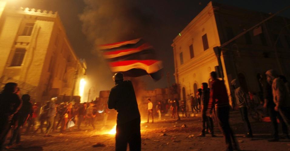 25.jan.2013 - Manifestantes segura a bandeira do Egito emfrente às chamas provocadas por coquetéis molotov, durante protestos próximos à praça Tahrir, no Cairo. Nesta sexta-feira (25), data que marca os dois anos das revoltas que derrubaram o ditador Hosni Mubarak, protestos contrários ao atual presidente Mohamed Mursi tomaram todo o país, com confrontos entre os manifestantes e a polícia