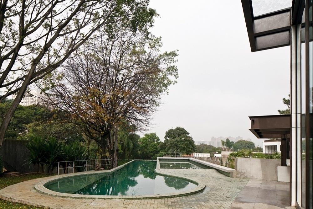 A piscina permanece no mesmo nível da sala de estar e da cozinha e tem acesso direto a partir das suas grandes portas de vidro. A raia semiolímpica, com 22,5m de comprimento, acompanha a direção da paisagem e da luz e segue rumo aos pontos mais baixos e mais verdes (fundos) do terreno. A vista ao longe é para o Parque Vila Lobos, em São Paulo. O projeto de arquitetura é assinado por Monica Drucker