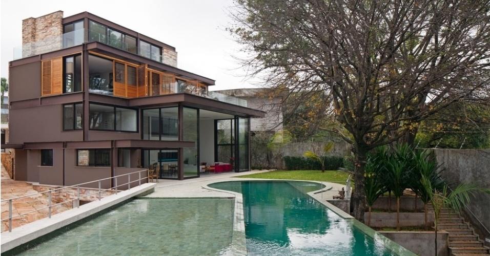 O terreno da casa AM está em um declive drástico a partir da fachada principal, junto à rua. A piscina, para ser mantida no mesmo nível da sala de estar e da cozinha e com acesso direto a partir delas, teve de ser suspensa por grande estrutura de concreto, formando uma espécie de marquise impermeabilizada (Vedacit). A arquitetura é de Monica Drucker