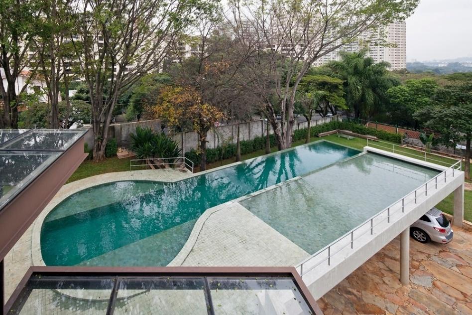 Todo o entorno e o interior da piscina estão revestidos por pedra Bali (10 cm x 10 cm) ? cuja cor muda de acordo com a profundidade da água. Porosa, a pedra assume tons de verde que se intensificam à luz do sol, em visão bastante tropical. A casa AM tem arquitetura assinada por Monica Drucker