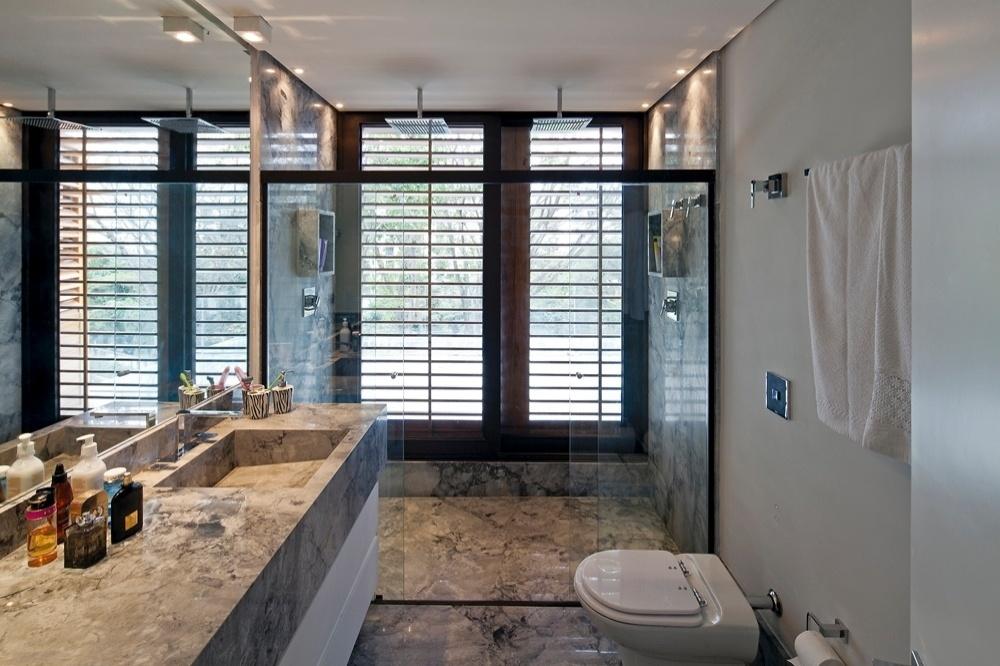 Um dos banheiros da casa AM, com arquitetura de Monica Drucker, é inteiramente revestido com mármore italiano carrara, só que de tonalidade mais escura, próxima do cinza. Os metais, louças e o chuveiro pendente Quadratta são da Deca