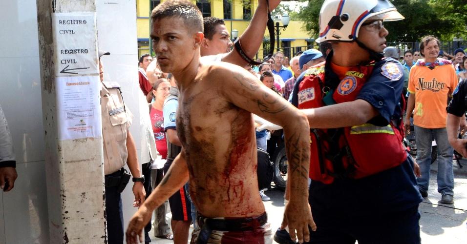 25.jan.2013 - Socorrista conduz um homem não identificado durante rebelião no presídio de Uribana, na cidade de Barquisimeto, noroeste da Venezuela. O motim explodiu após a imprensa do país divulgar, inadvertidamente, uma operação de busca de armas dentro da penitenciária feita pela polícia venezuelana. Ao menos 61 pessoas morreram e 120 ficaram feridas na ação para controlar os detentos