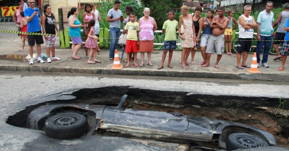 26.jan.2013 - Carro cai em cratera na avenida Jornalista Roberto Marinho, em São Gonçalo (RJ)