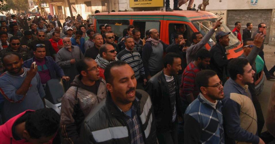 26.jan.2013 - Manifestantes protestam ao redor de ambulância que carregava o corpo de uma pessoa que morreu na sexta-feira (25) em confrontos com a polícia, em Suez, no Egito