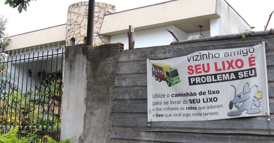 27.jan.2013 - Cartaz criticando o lixo jogado no local, que atrai ratos para o terreno, é colocado em portão da alamedas dos Imarés, no bairro Planalto Paulista, zona sul da cidade de São Paulo (SP), neste domingo (27)