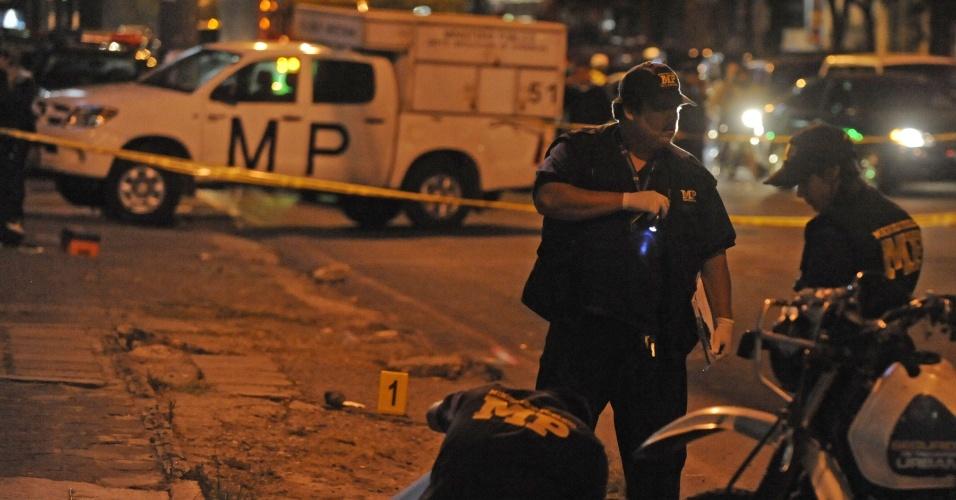 27.jan.2013 - Policiais inspecionam o corpo de Nolberto Hernandez, policial morto a tiros por homens armados não-identificados, na cidade da Guatemala