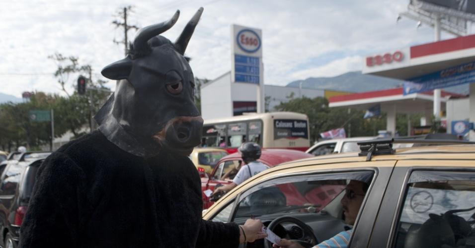 27.jan.2013 - Usando máscara de touro, homem distribui panfleto no trânsito de Medellín (Colômbia) durante protesto contra as touradas