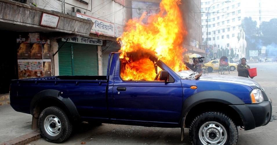 28.jan.2013 - Bengalês usa um balde para tentar apagar fogo em um carro de polícia, supostamente ateado por membros do partido islâmico Jamaat-e-Islami, em Dacca, Bangladesh, nesta segunda-feira (28). Ativistas islâmicos entraram em choque com a polícia, jogando bombas de gasolina e tijolos para protestar contra o julgamento de seus líderes por alegados crimes de guerra