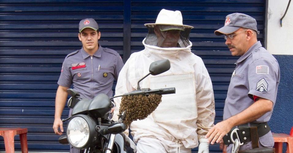 28.jan.2013 - Corpo de bombeiros é chamado para retirar um enxame de abelhas que parou em uma moto estacionada na frente de um bar no bairro Campos Elíseos, em Ribeirão Preto (SP), nesta segunda-feira (28). O plano traçado foi andar com a moto para ver se elas se dissipavam com o vento. Para isso um dos bombeiros teve que vestir uma roupa especial e sair com a moto