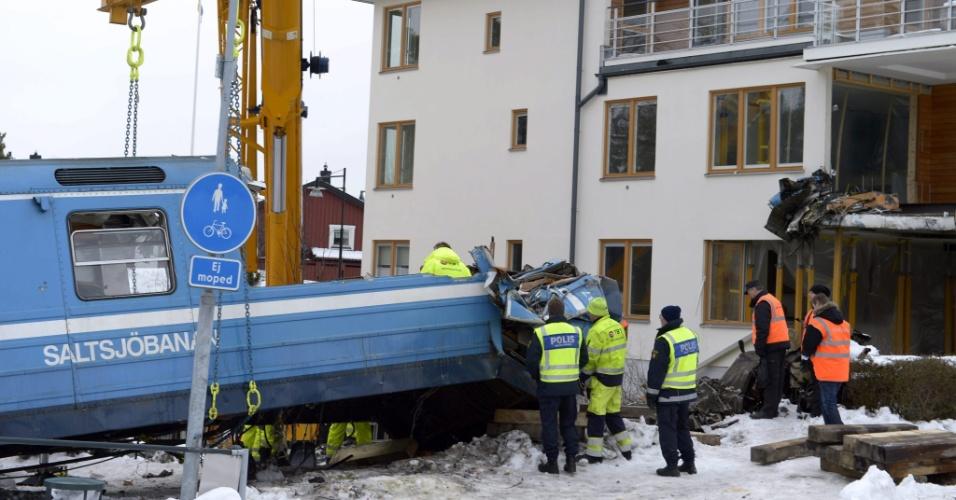 28.jan.2013 - Equipes trabalham nesta segunda-feira (28) no resgate de um trem que se chocou contra um bloco de apartamentos no último dia 15, em Saltsjoebaden, nos arredores de Estocolmo, na Suécia. A princípio, a polícia acreditava que o trem havia sido tomado por ladrões, mas a hipótese foi descartada. Acredita-se que foi um acidente, e não houve mortes