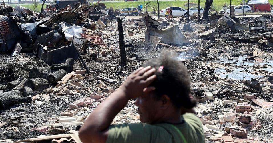 28.jan.2013 - Moradores buscam pertences em meio aos destroços do incêndio na Vila Liberdade, em Porto Alegre (RS), nesta segunda-feira (28). Um incêndio atingiu a comunidade neste domingo (27). Os moradores procuram principalmente documentos e objetos pessoais