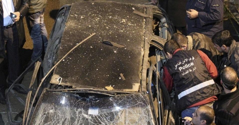 28.jan.2013 - Policiais inspecionam carro danificado por bomba, em bairro de  Beirute (Líbano). As autoridades locais afirmaram que o episódio pode ter sido provocado por grupo extremista