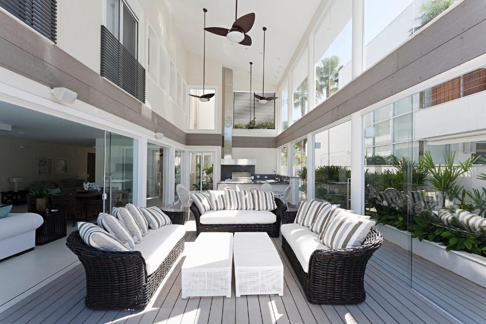 Em outra varanda gourmet projetada pela arquiteta Selma Tammaro, o amplo espaço disponível permitiu dispor três sofás com acabamento indicado para o uso em áreas externas, além das mesas redondas para refeições (ao fundo)