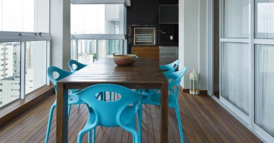 Em outra varanda gourmet projetada pelos arquitetos Olegário Sá e Gilberto Cioni, as cadeiras na tonalidade azul vibrante contrastam com a predominância da madeira (piso e mesa)