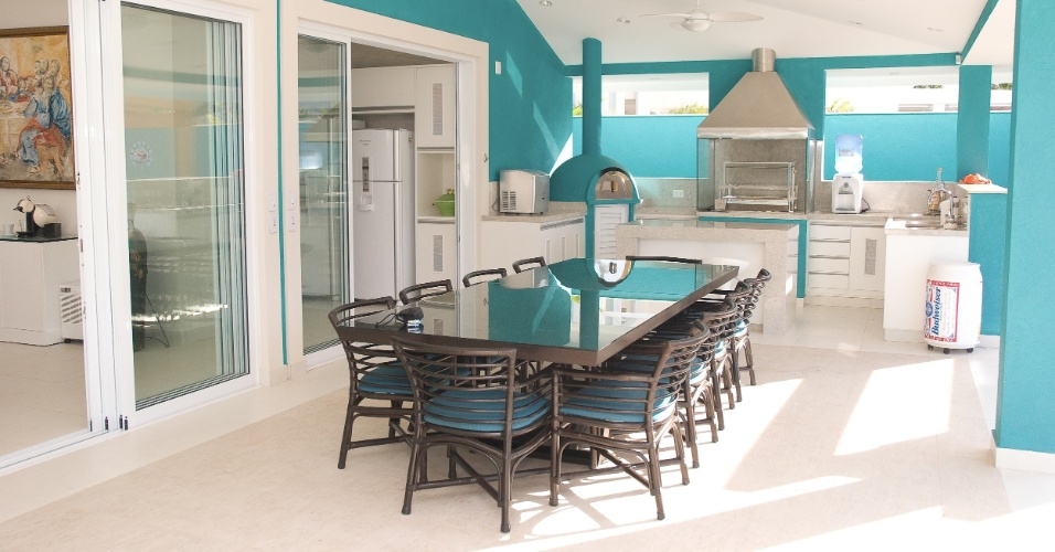 Integrada à cozinha, a varanda gourmet assinada pela arquiteta Selma Tammaro conta com mesa central, churrasqueira e forno para pizza